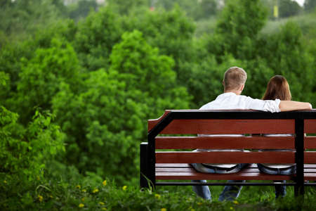 enamoured: The enamoured couple sits on a bench against green trees Stock Photo