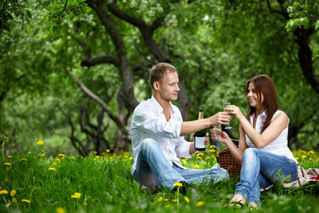 The young couple drinks champagne in wood photo