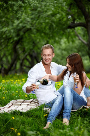 The attractive enamoured couple drinks champagne in park photo