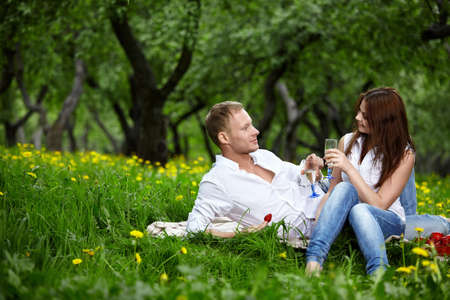 The young couple in park on picnic drinks champagne photo