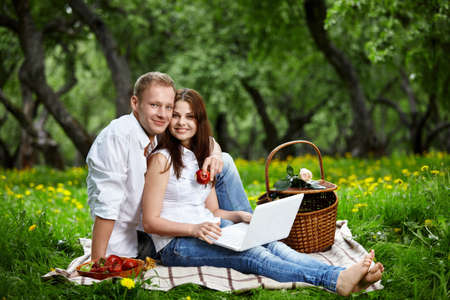 Happy couple on picnic with the laptop in wood photo