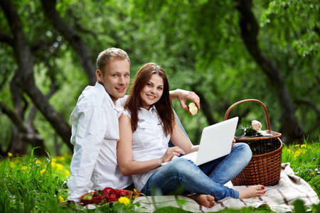 Young nice couple with the laptop in forest photo