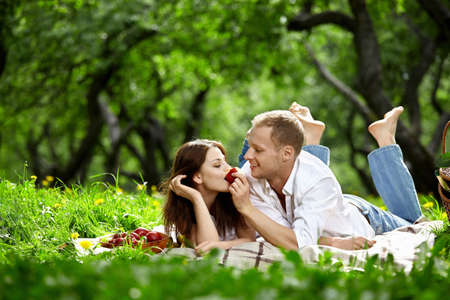 woman eat: Young enamoured couple on picnic in wood