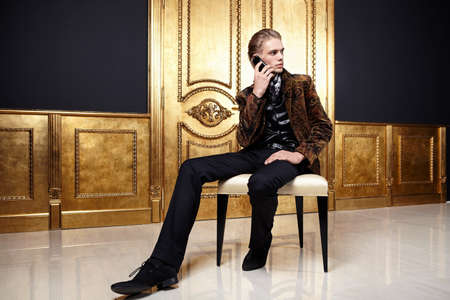 The young man speaks by phone in a gold interior Stock Photo - 7861610