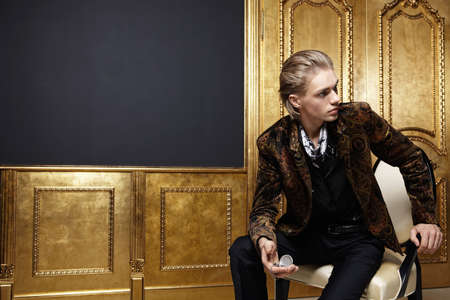 The sitting young man with watch against a gold door photo