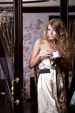The beautiful girl with a cup in a hand at restaurant photo