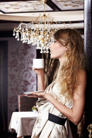 chandeliers: The attractive girl with a white cup on a forward background
