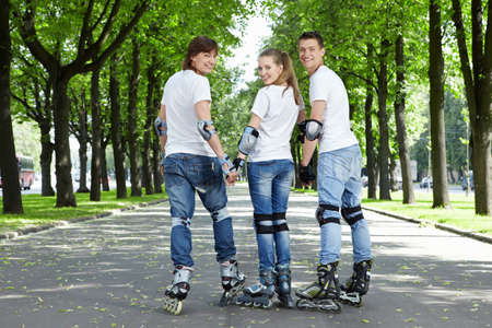 Three young scooters stand having turned back in park photo