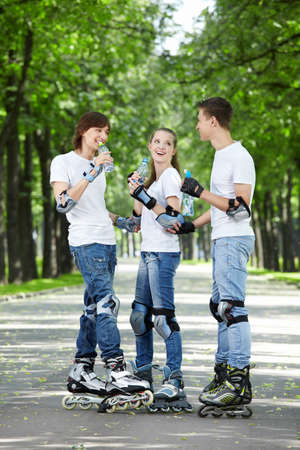 Three young people on rollers drink water Stock Photo - 7861618