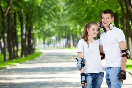 enamoured: Young enamoured couple on rollers in park Stock Photo