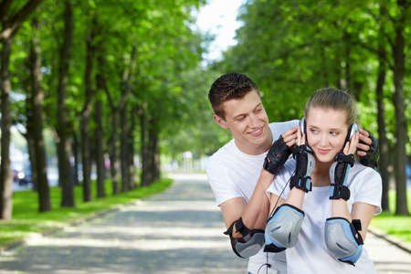 The young man looks at the girl listening to music in ear-phones in park Stock Photo - 7861557