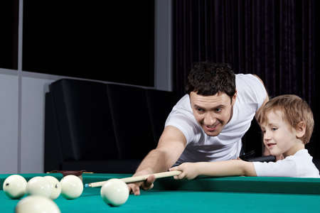 The father and the son play billiards photo
