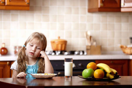 The little girl looks at a plate with a breakfast on kitchen   photo
