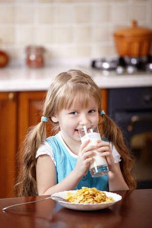 The little girl drinks milk for a breakfast photo