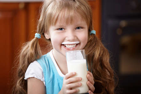 The girl with a milk glass on kitchen