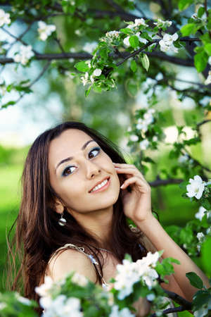 Attractive girl on a background of flowering trees photo