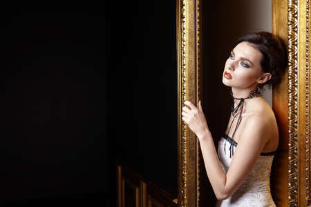 The beautiful girl with a make-up at a gold door photo