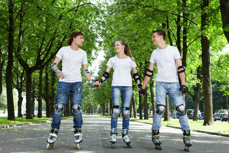 Three young people riding on roller skates holding hands photo