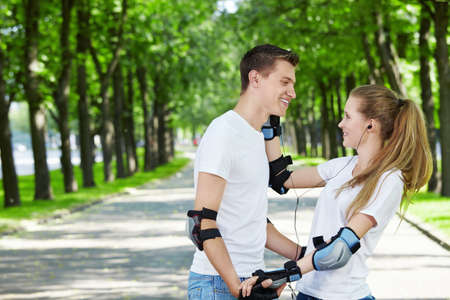 The girl in park gives an ear-phone to the man Stock Photo - 7952554