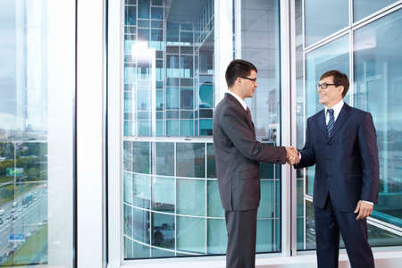 business deal: Two business people shake hands in the office Stock Photo