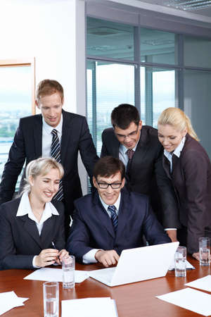 Business people looking at laptop in office photo