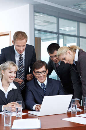 Employees with the boss looking at laptop monitor photo