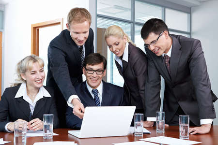 Five business people in suits discussing something with laptop photo