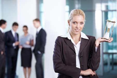 zeitarbeit: Business-Frau mit Sanduhr im Vordergrund