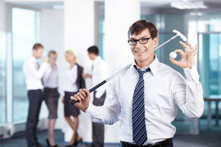 Businessman with a golf club against the staff office Stock Photo - 7944920