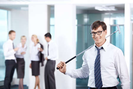 A man with a golf club against a background of office workers photo
