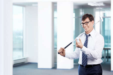 golfers: Business man with a golf club in office