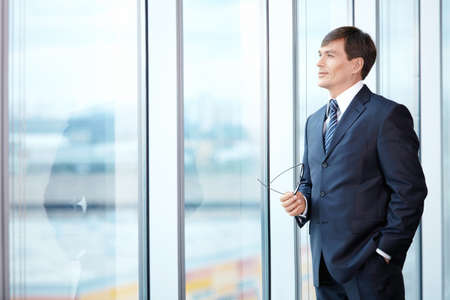 one mature man only: A man in a business suit looks out the window Stock Photo