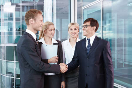 Business people shake hands with each other photo