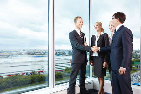 two hands: Two businessmen shake hands next to business women