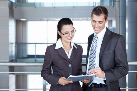 2 pessoas: Two young business people looking documents Imagens