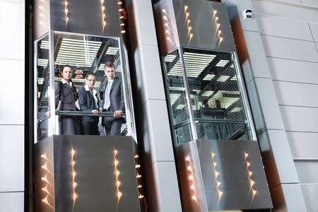 people in elevator: Business people traveling in the elevator looking down
