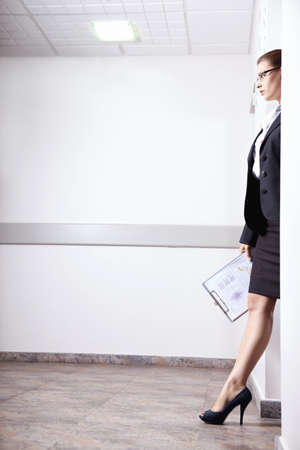 A young girl in a serious suit goes out the door photo