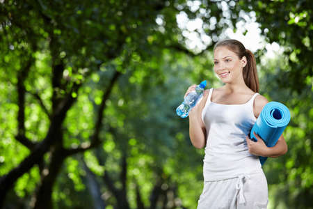 Young girl with a bottle of water and gymnastic mat photo