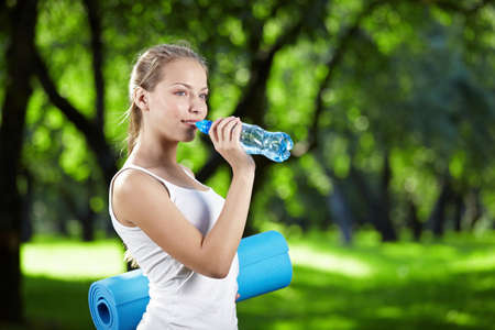 Young attractive girl drinking water and keeps the gym mat photo