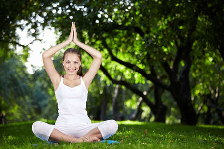 An attractive girl in a pose of yoga outdoors photo