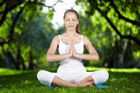 mujer meditando: Una joven mujer meditando en Parque