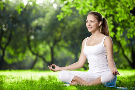 breathe: Woman in lotus pose in the park Stock Photo