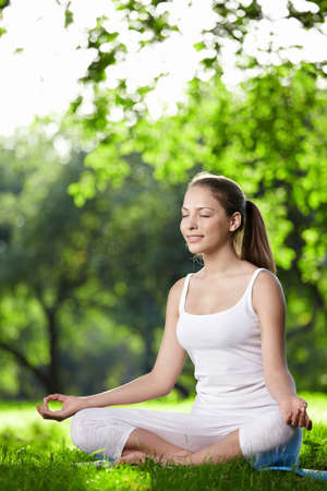 A young woman practices yoga in the park Stock Photo - 7944949