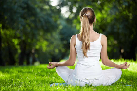 A girl in one of the yoga postures back outdoors photo