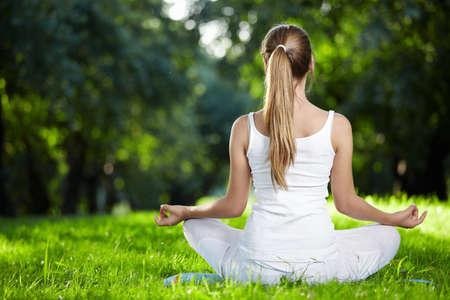 mujer meditando: Una niña en una de las posturas de yoga volver al aire libre