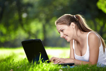 nice girl: Nice girl looking at laptop monitor in the park Stock Photo