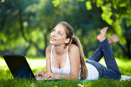 barefoot women: Dreamy girl with a laptop in the park