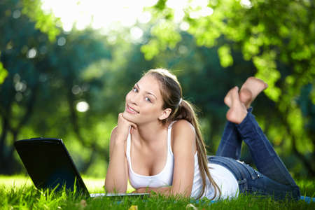 A beautiful young girl with laptop in the park photo