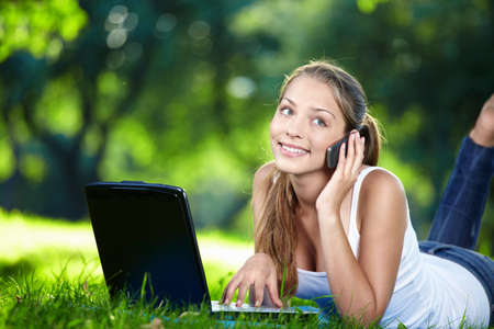 Attractive girl with laptop talking on the phone photo