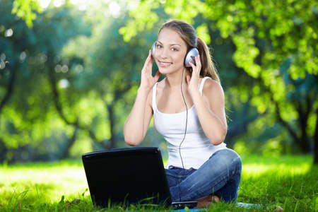 Girl with headphones and a laptop in the park photo